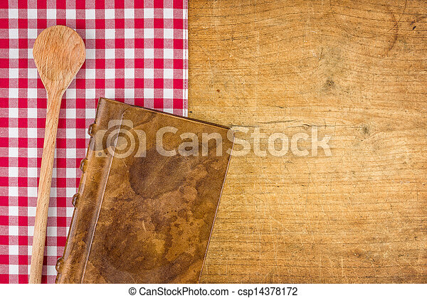 Wooden spoon and book on a wooden board with a checkered tablecloth - csp14378172