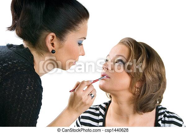 Makeup artist applying lipstick using lip concealer brush - csp1440628