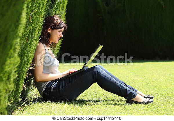 Attractive woman happy in a park with a laptop - csp14412418