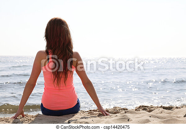 Beach holidays woman enjoying summer sun sitting in sand looking happy at copy space. Beautiful young model - csp14420475