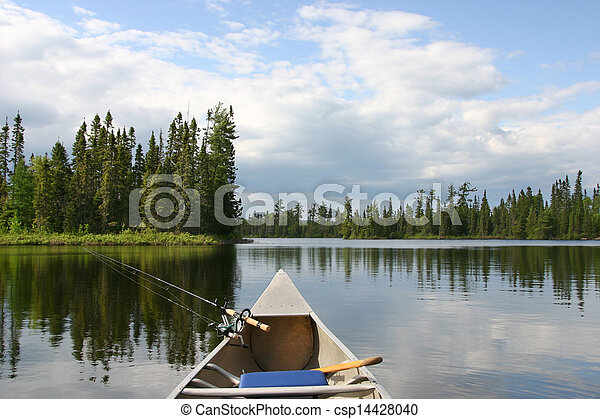Canoe with fishing gear heading out on northern lake - csp14428040