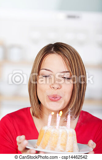 Woman blowing out her birthday candles - csp14462542