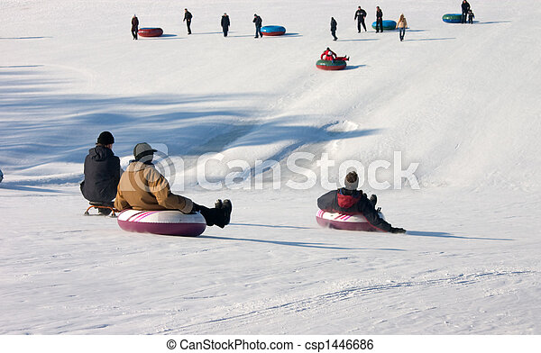 People slide down from a snow hill