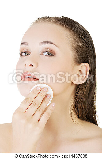 Happy young woman cleaning skin by cotton pad