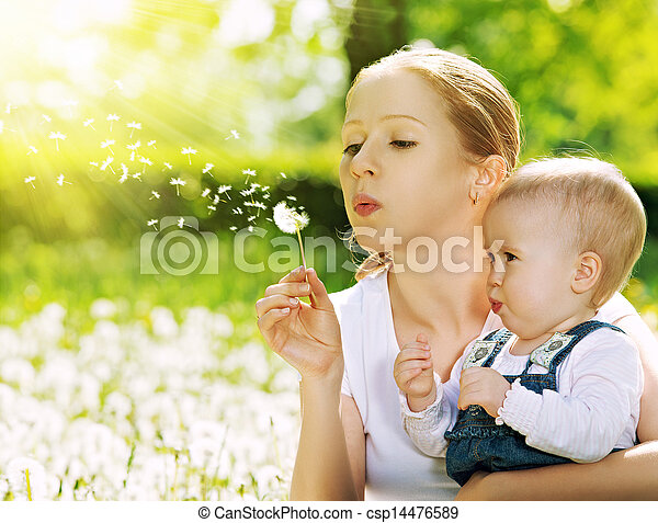 happy family. Mother and baby girl blowing on a dandelion flower on the nature in the summer in the park - csp14476589