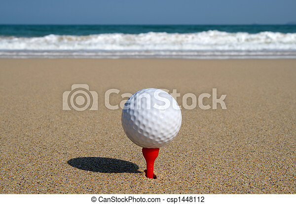 Golf ball on the beach, ready to be hit in to the ocean. - csp1448112