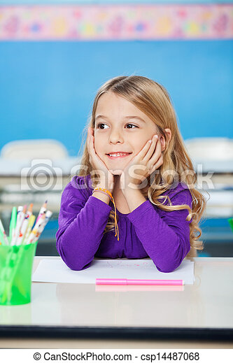 Girl Smiling While Sitting With Head In Hands At Desk