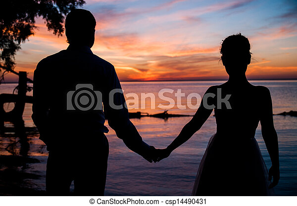 Young couple standing on a beach and looking to a sunset sky - csp14490431