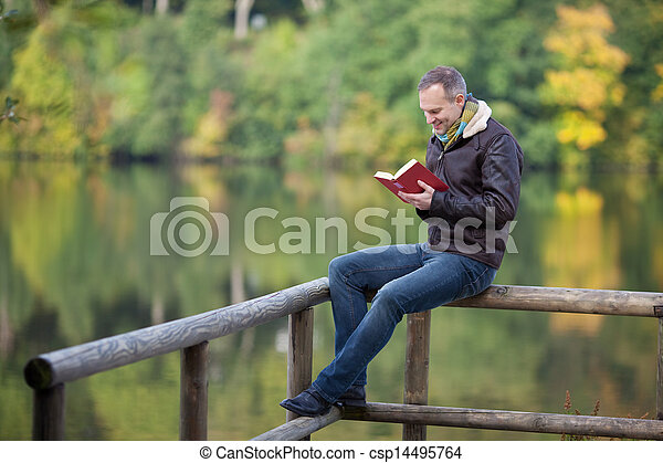 Man Reading Book While Sitting On Fence Against Lake - csp14495764