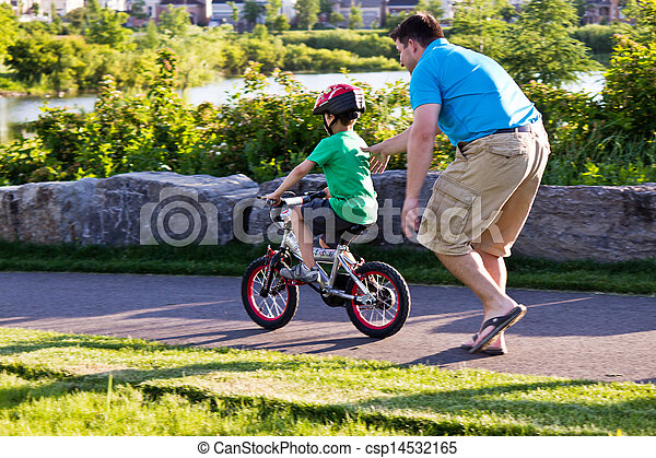 Child learning to ride a bicycle with father - csp14532165