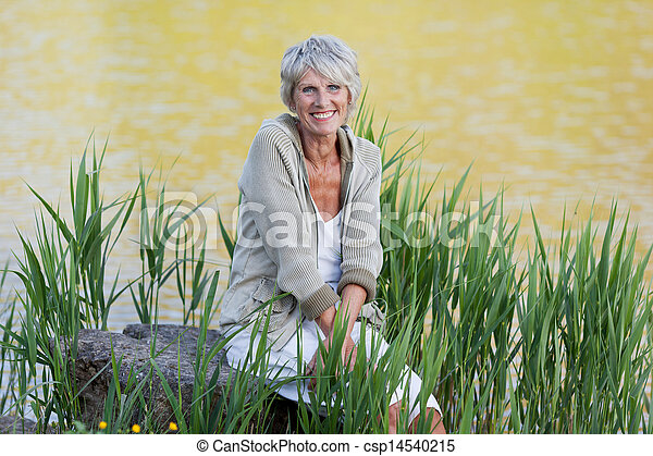 Cheerful old lady sitting near the lake - csp14540215