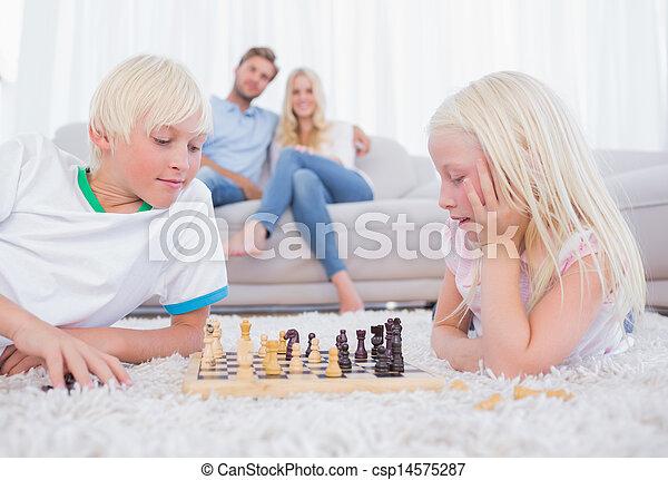 Cute siblings playing chess