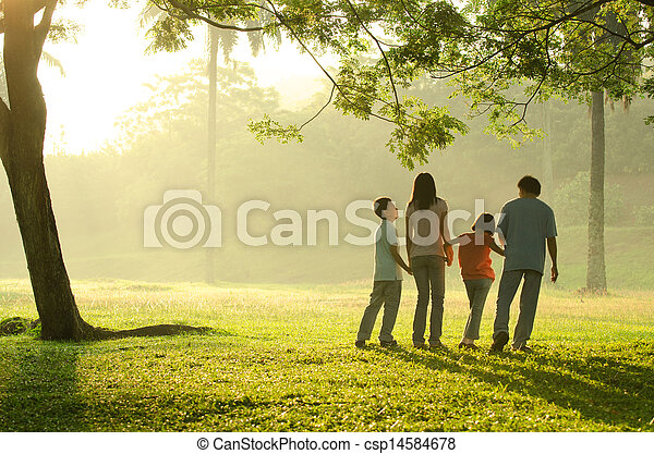 silhouette of a family walking in the park during a beautiful sunrise, backlight - csp14584678