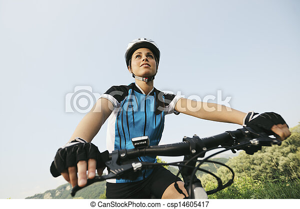 young woman training on mountain bike and cycling in park - csp14605417