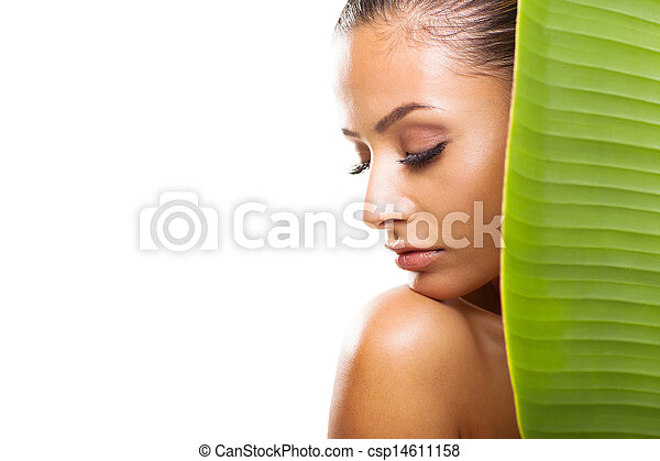 young woman with eyes closed behind large green leaf - csp14611158