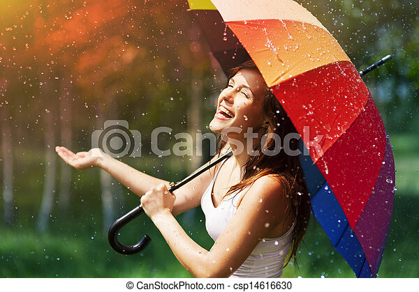 Laughing woman with umbrella checking for rain - csp14616630
