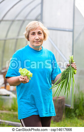 Happy senior Caucasian woman with onion and lettuce standing against greenhouse