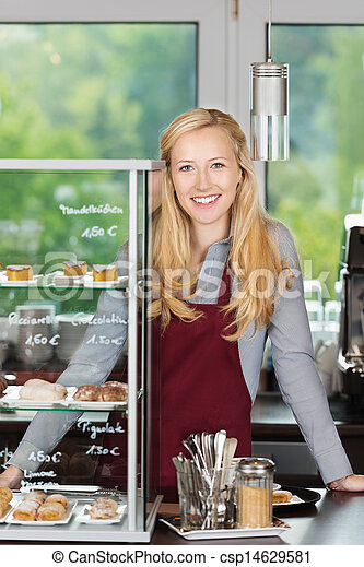 smiling waitress leaning on coffee shop counter