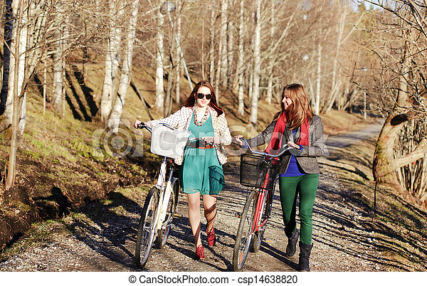 Two girls walking with bikes in the park - csp14638820