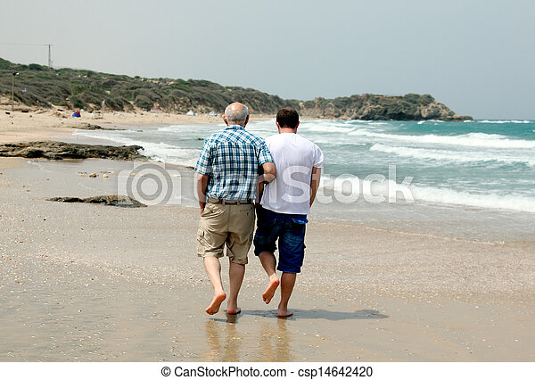 adult son and father walking together on the beach - csp14642420