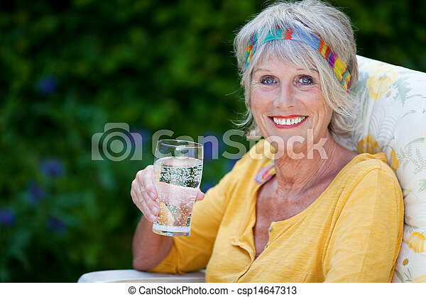 elderly lady holding a glass of water - csp14647313