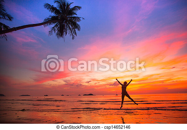 Young girl in a jump on the sea beach at sunset (concept of long-awaited vacation) - csp14652146