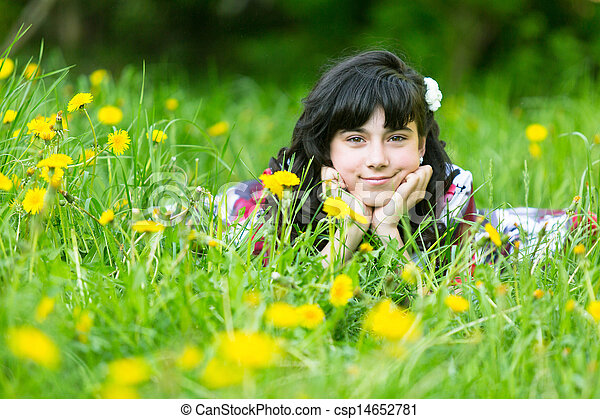 Pretty young girl lying in the grass in the park - csp14652781