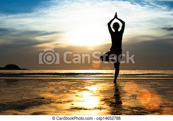 Silhouette of a young woman practicing yoga on the beach at sunset.  - csp14652788