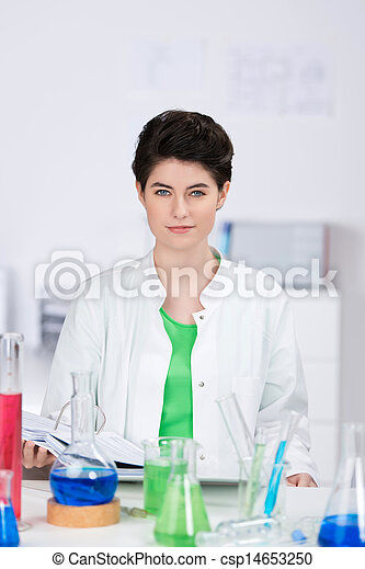 Female Scientist With Chemicals On Desk In Laboratory - csp14653250