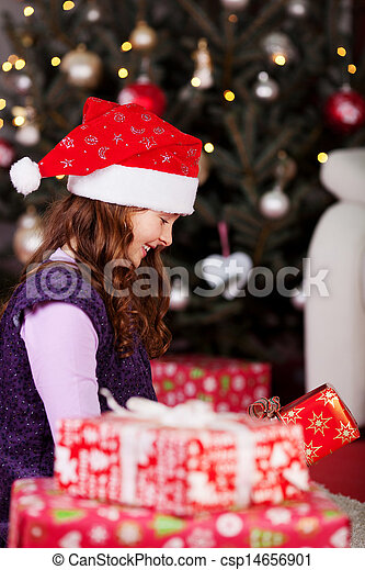 Little girl unwrapping Christmas gifts