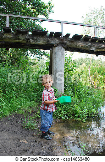 In the summer, outdoors, near the river and bridges, the little boy is playing with a ladle - csp14663480