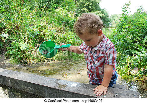 In the summer, outdoors, near the river and bridges, the little boy is playing with a ladle - csp14663497