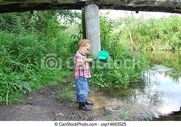 In the summer, outdoors, near the river and bridges, the little boy is playing with a ladle - csp14663525