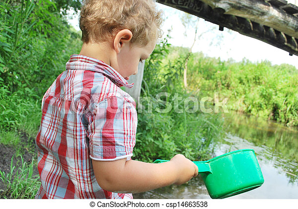 In the summer, outdoors, near the river and bridges, the little boy is playing with a ladle - csp14663538