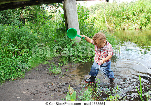In the summer, outdoors, near the river and bridges, the little boy is playing with a ladle - csp14663554