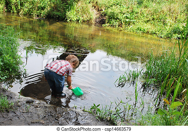 In the summer, outdoors, near the river and bridges, the little boy is playing with a ladle - csp14663579