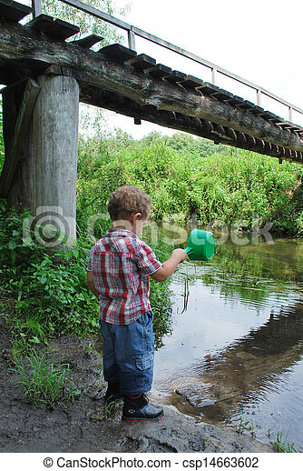 In the summer, outdoors, near the river and bridges, the little boy is playing with a ladle - csp14663602
