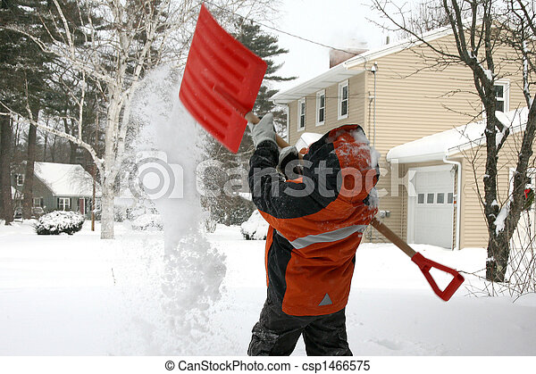 Five year old boy shoveling snow covered driveway in Maine.