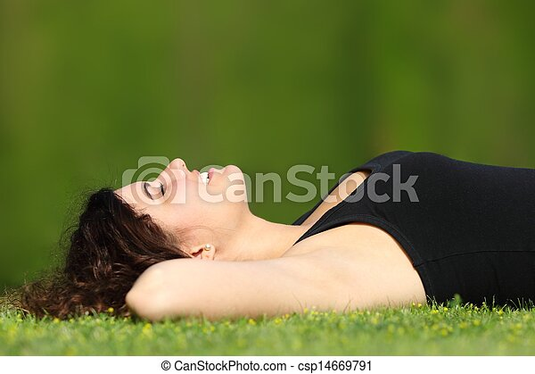 Attractive woman relaxed lying on the grass in a park - csp14669791
