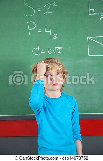 Sad Schoolboy Standing Against Board In Classroom