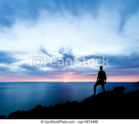 Man hiking silhouette in mountains, ocean and sunset - csp14674489