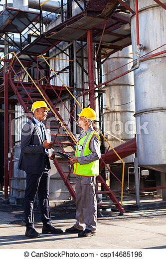 petrochemical manager in discussion with plant worker - csp14685196