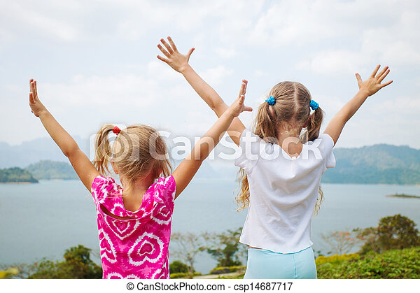 two girls near a lake pulling his hands to heaven - csp14687717