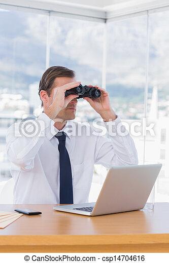 Businessman using binoculars while he is working - csp14704616