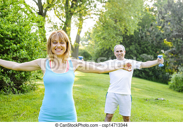 Personal trainer with client exercising outside - csp14713344