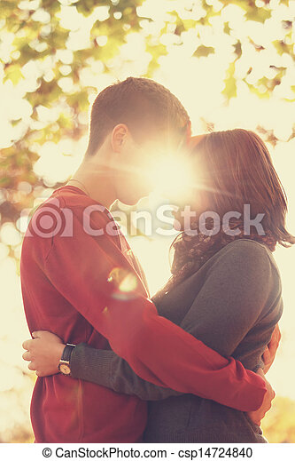 Couple gonna kissing in the park at sunset. Photo in multicolor image style. - csp14724840