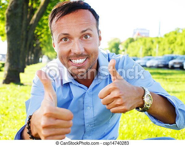 Happy handsome middle-aged man showing thumbs up outdoors - csp14740283
