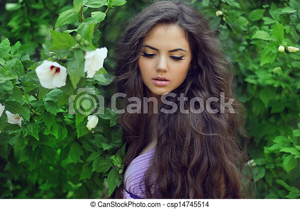 Beautiful Woman with Curly Long Hair. Outdoors Portrait on green background, resting in park - csp14745514