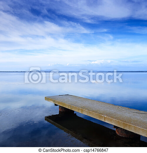 Concrete pier or jetty and on a blue lake and sky reflection on water. - csp14766847