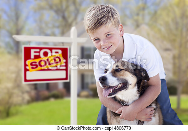 Young Boy and His Dog in Front of Sold For Sale Sign and House - csp14806770